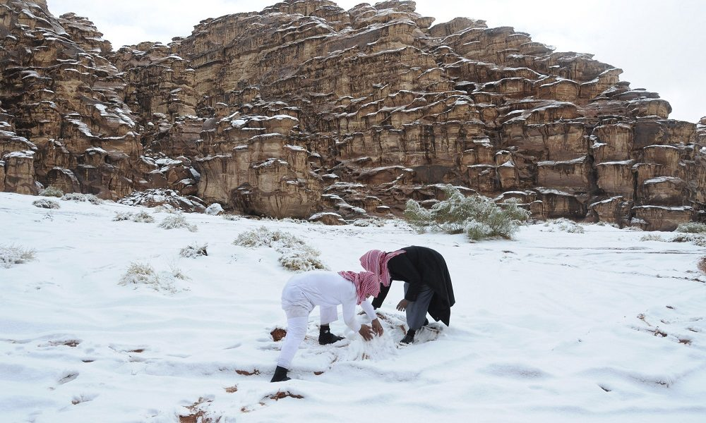 Saudi men make a snowman after a snowstorm in Alkan village, west of Saudi Arabia December 13, 2013.  REUTERS/Mohamed Alhwaity (SAUDI ARABIA - Tags: ENVIRONMENT SOCIETY) - RTX16H71
